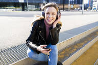 Portrait of young woman listening music with smartphone and headphones, Barcelona, Spain - GIOF06615
