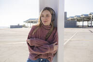 Portrait of smiling young woman  listening music with wireless headphones, Barcelona, Spain - GIOF06624