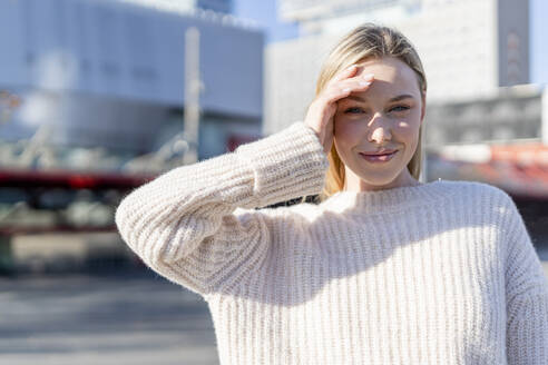 Portrait of smiling young woman  shiedling eyes with her hand - GIOF06627