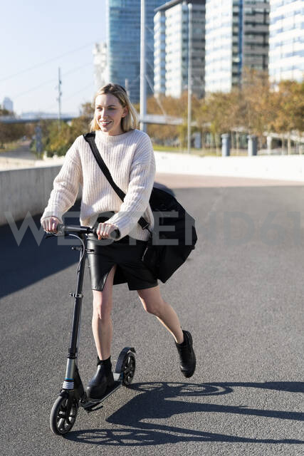 Smiling young woman with sports bag riding kick scooter - GIOF06639 - Giorgio Fochesato/Westend61