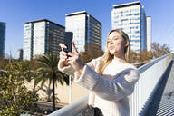 Portrait of blond young woman on footbridge talking selfie with smartphone - GIOF06651