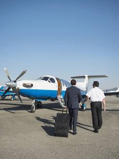 Caucasian businessmen walking on runway - BLEF09225