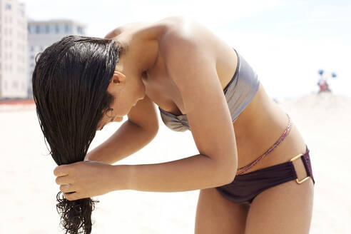 Mixed race woman wringing out her hair on beach - BLEF09267