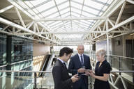 Business people using smart phone and digital tablet on office atrium balcony - HEROF36932