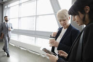 Businesswomen using digital tablet in office corridor - HEROF36938