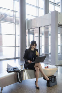 Businesswoman eating sandwich, working at laptop in office lobby - HEROF36953