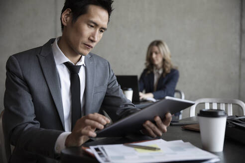 Businessman using digital tablet at cafe table - HEROF36995