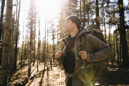 Serene man with backpack hiking ins sunny woods - HEROF37124