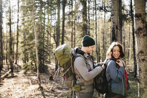 Couple with backpacks hiking in woods - HEROF37130