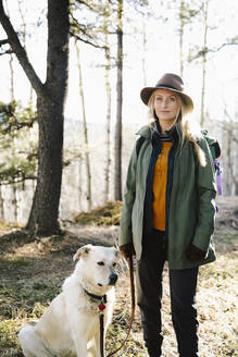 Portrait confident woman with dog hiking in woods - HEROF37142