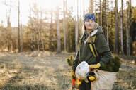 Female volunteer planting trees in woods - HEROF37151