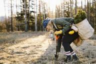 Female volunteer planting trees in woods - HEROF37157