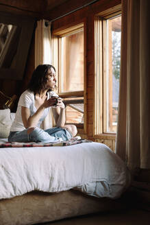 Serene woman drinking coffee on cabin bed - HEROF37163