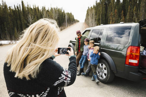 Woman with camera phone photographing family outside SUV at remote roadside - HEROF37178