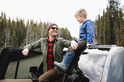Happy father and son outside SUV at remote roadside - HEROF37181