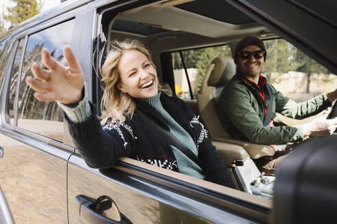 Carefree woman enjoying road trip in SUV - HEROF37190