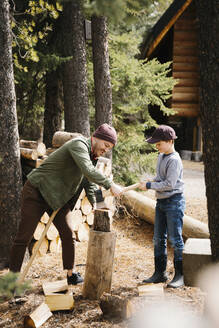 Father teaching son how to cut firewood outside cabin - HEROF37208