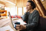 Smiling woman using laptop at cabin kitchen - HEROF37238