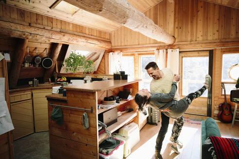 Playful couple dancing in cabin - HEROF37241