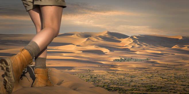 Caucasian woman hiking in desert sand dunes - BLEF09370