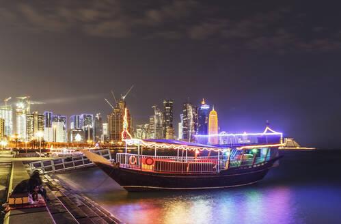 Illuminated boat docked in Doha harbor, Doha, Qatar - BLEF09379