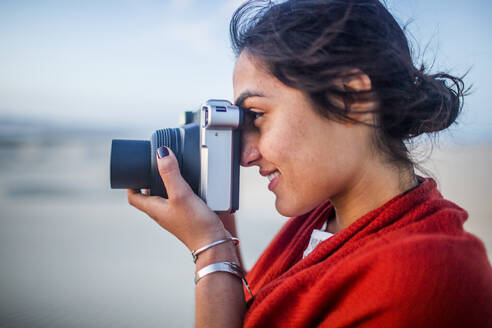 Mixed race woman photographing in desert - BLEF09418
