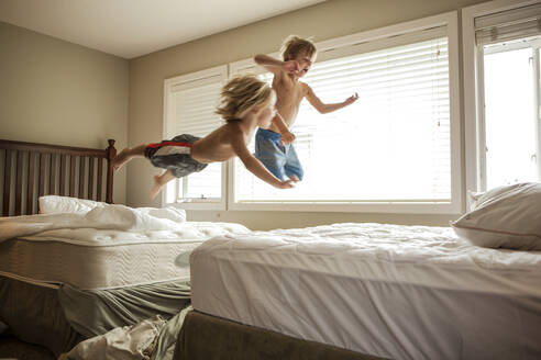 Caucasian boys jumping on beds - BLEF09426