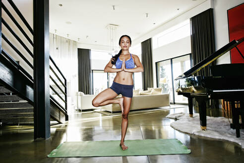 Chinese woman practicing yoga in living room - BLEF09450