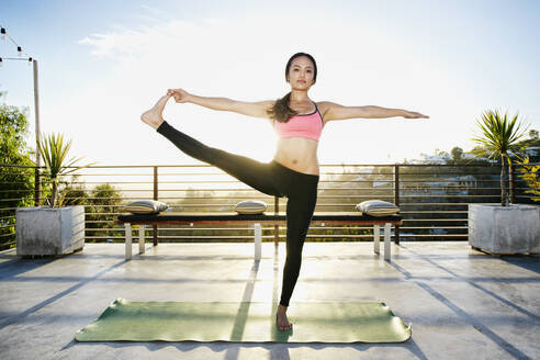 Chinese woman practicing yoga on balcony - BLEF09453