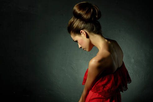Caucasian woman wearing red evening gown and hair bun - BLEF09471