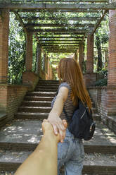 Young woman holding hands in front of pergola - AFVF03570