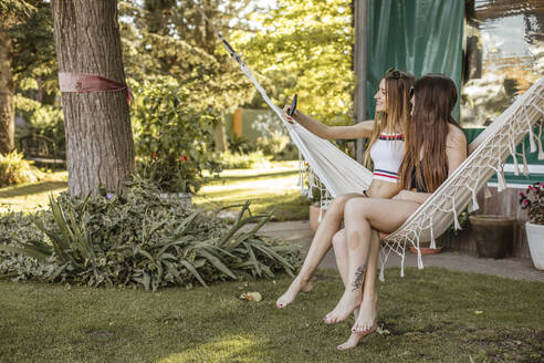 Two young women sitting on hammock in the garden taking selfie with mobile phone - ACPF00558