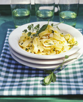 Pasta, tagliatelle noodles with herb sauce and pine nuts in a plate on a garden table - PPXF00205