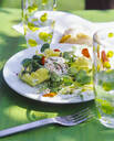 Close up of goat cheese with lettuce outside in garden on table - PPXF00208
