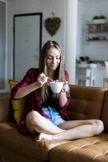Relaxed young woman eating cereals in living room at home - GIOF06662