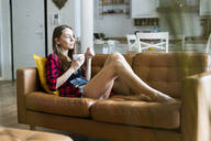 Relaxed young woman eating cereals in living room at home - GIOF06665