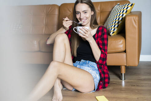 Portrait of happy young woman eating cereals in living room at home - GIOF06668