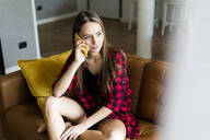 Young woman on cell phone on a couch at home - GIOF06674