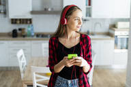 Young woman with cell phone and headphones at home - GIOF06689
