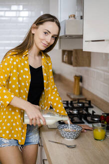 Portrait of young woman preparing breakfast on kitchen counter at home - GIOF06695