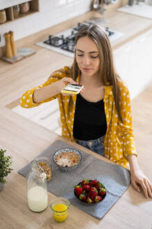 Young woman taking cell phone picture of her breakfast at home - GIOF06704