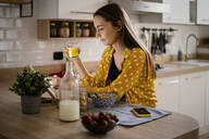 Young woman using tablet and having breakfast in kitchen at home - GIOF06707