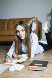 Portrait of smiling young woman lying on the floor at home taking notes - GIOF06713