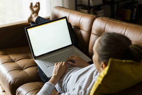 Young woman lying on couch at home using laptop - GIOF06722