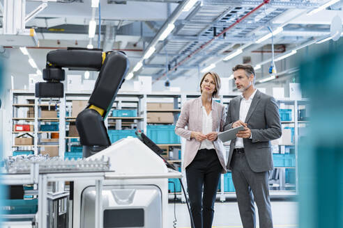 Businessman and businesswoman in a modern factory hall looking at robot - DIGF07208