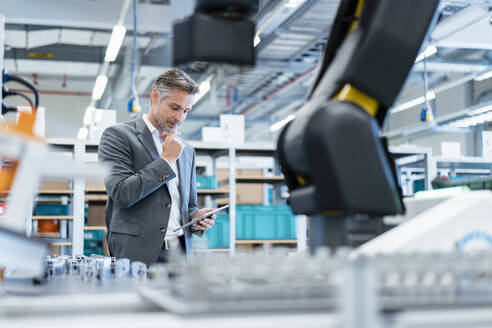 Businessman with tablet in a modern factory hall - DIGF07214