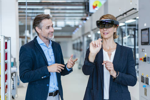 Businesswoman with AR glasses and businessman in a modern factory - DIGF07253