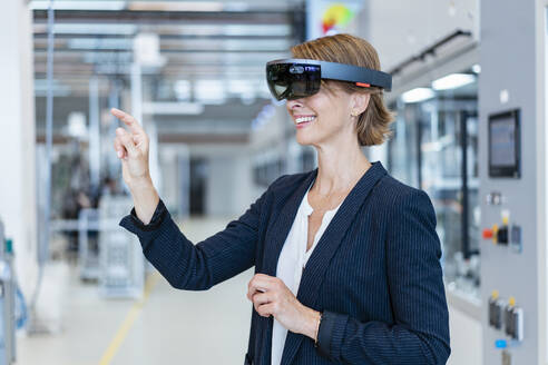 Smiling businesswoman wearing AR glasses in a modern factory - DIGF07256