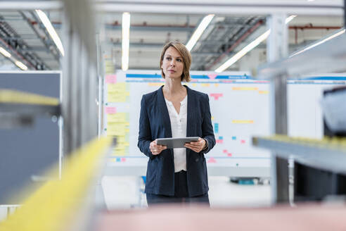 Businesswoman with tablet in a factory hall - DIGF07277