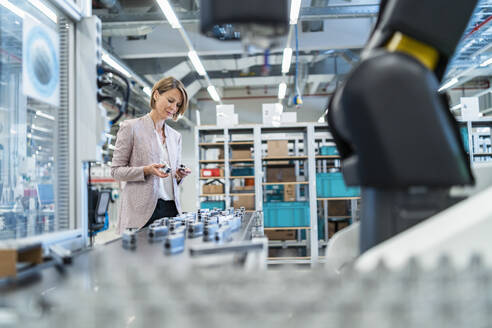 Businesswoman examining workpieces in a modern factory hall - DIGF07304